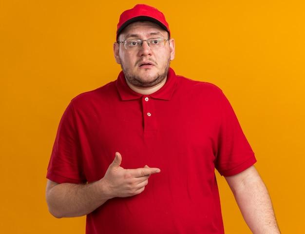 Ängstlicher übergewichtiger junger zusteller in optischer brille, der auf die seite zeigt, isoliert auf oranger wand mit kopierraum isolated