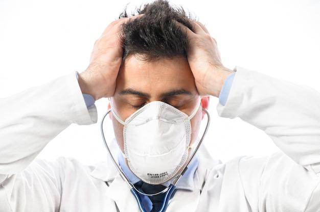 Ängstlicher und nervöser arzt. nahaufnahmeporträt eines arztes in schützender gesichtsmaske mit besorgtem ausdruck, der seine hände auf den kopf legte. ausbruch des pandemie-coronavirus.