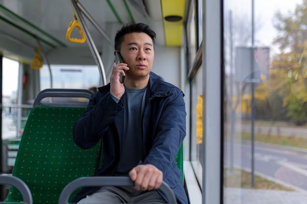Ängstlicher und verängstigter asiatischer mann, der einen öffentlichen bus fährt, ein passagier, der mit einem mobiltelefon telefoniert