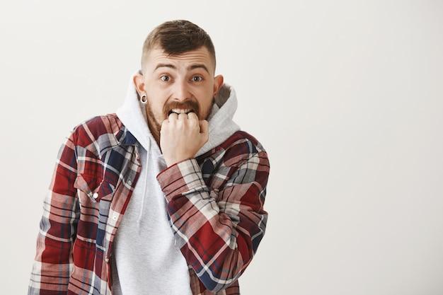Ängstlicher und verängstigter hipster-typ, der sich die faust beißt, macht sich sorgen
