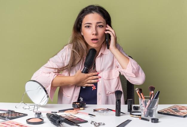 Ängstliches junges brünettes mädchen, das am tisch mit make-up-tools sitzt und am telefon spricht und den kamm isoliert auf olivgrüner wand mit kopienraum hält?