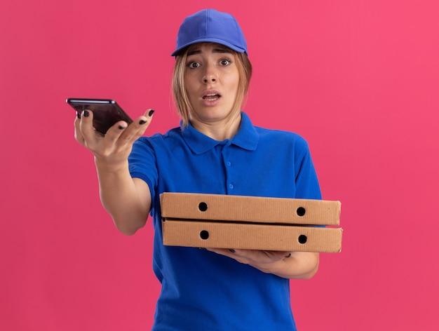 Ängstliches junges hübsches liefermädchen in uniform hält pizzaschachteln und telefon auf rosa