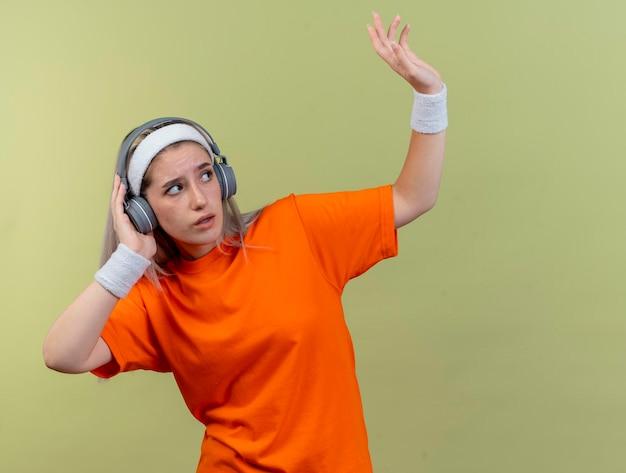 Ängstliches junges kaukasisches sportliches mädchen mit klammern auf kopfhörern, die stirnband tragen