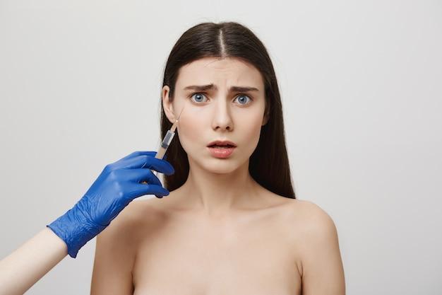 Ängstliches junges mädchen, das injektion von botox macht