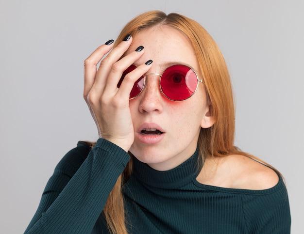 Ängstliches junges rothaariges ingwermädchen mit sommersprossen in sonnenbrille, das hand auf gesicht legt