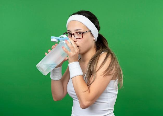 Ängstliches junges sportliches mädchen in optischer brille mit stirnband und armbändern trinkt aus einer wasserflasche