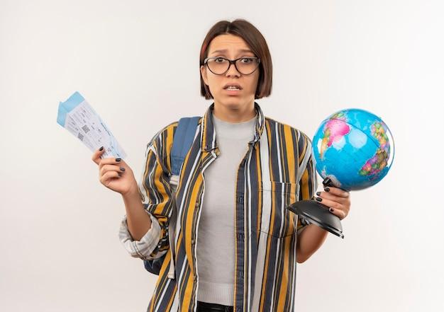 Ängstliches junges studentenmädchen, das brille und rückentasche hält, die flugtickets und globus lokalisiert auf weiß halten