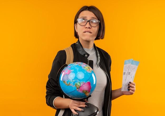 Ängstliches junges studentenmädchen, das brille und rückentasche hält globus und tickets, die seite lokalisiert auf orange mit kopienraum halten
