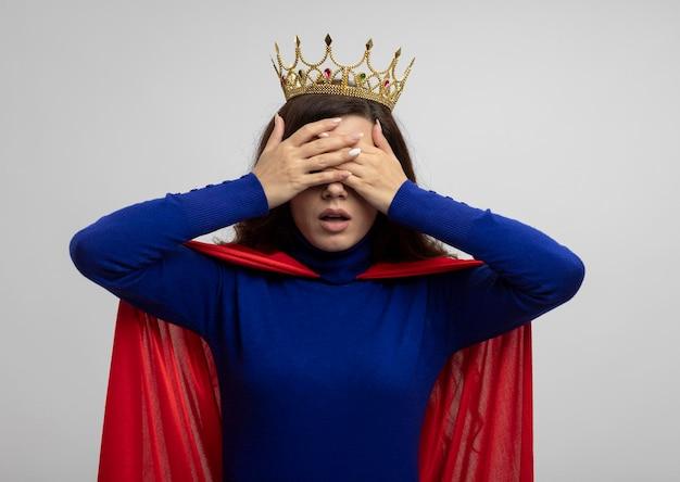 Ängstliches kaukasisches superheldenmädchen mit krone und rotem umhang bedeckt augen mit händen auf weiß