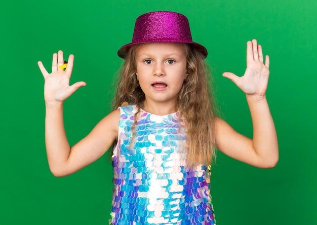 Ängstliches kleines blondes mädchen mit lila partyhut stehend mit erhobenen händen, die partypfeife lokalisiert auf grüner wand mit kopienraum halten