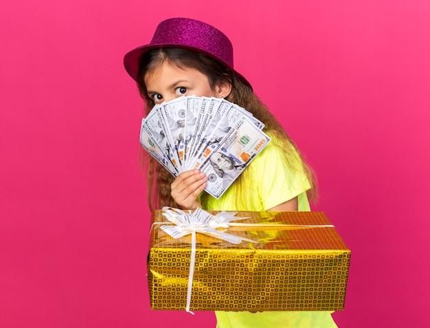 Ängstliches kleines kaukasisches mädchen mit lila partyhut, das geschenkbox und geld isoliert auf rosa wand mit kopienraum hält