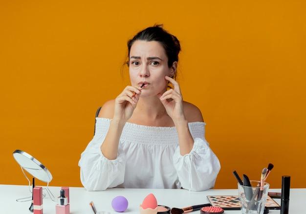 Ängstliches schönes mädchen sitzt am tisch mit make-up-werkzeugen beißt make-up-pinsel isoliert auf orange wand