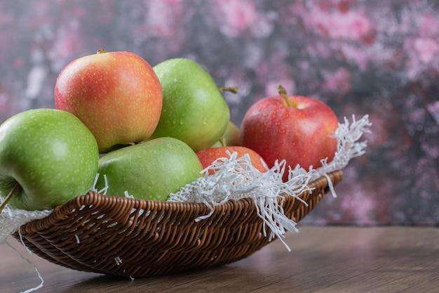Äpfel auf holzkorb auf weißer leinwand.