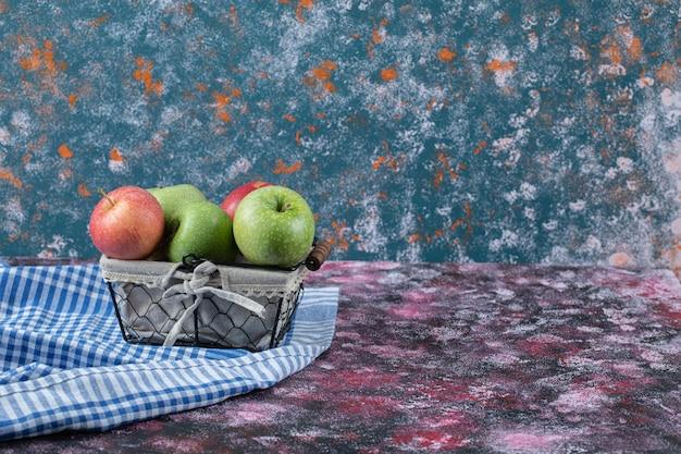 Äpfel auf metallischem moni-korb auf blau.