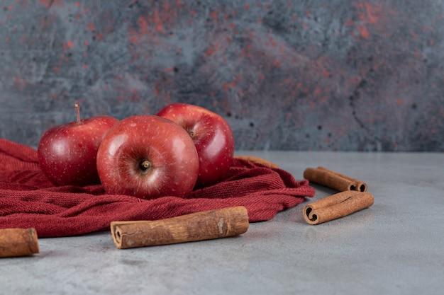 Äpfel auf tischdecke neben zimtstangen auf marmoroberfläche