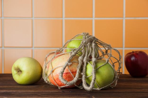 Äpfel der seitenansicht im netzbeutel auf hölzernem und orangefarbenem fliesenhintergrund. horizontal