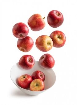 Äpfel, die über weiße schüssel fliegen, lokalisiert vom hintergrund
