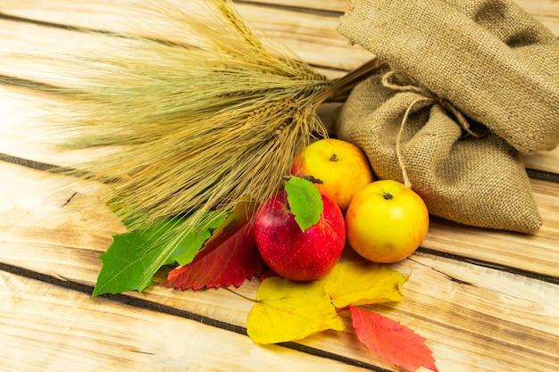 Äpfel, ein haufen weizen und eine tüte weizen auf einem holzplatz. erntedank. herbst themenraum.
