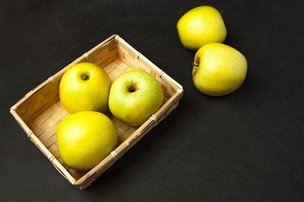 Äpfel. frische reife grüne äpfel im korb ordneten auf dunkler oberfläche an