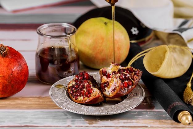 Äpfel, granatapfel und honig für rosch haschana tora buch