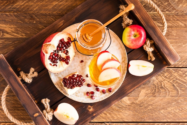 Äpfel, granatapfel und honig für rosh hashanah serviert auf einem holztablett.