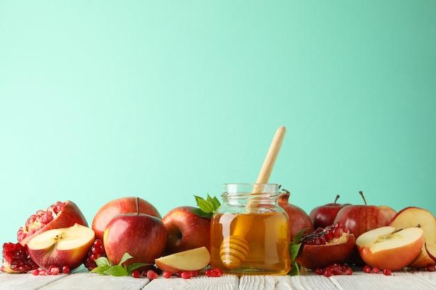 Äpfel, granatapfel und honig gegen minze, platz für text