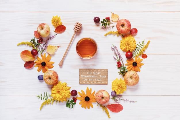 Äpfel, honig, pflaumen, rote beeren und schöne blumen