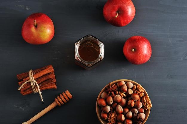 Äpfel, honig und nüsse auf dunklem tisch