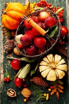 Äpfel im korb und herbstdekorationen auf altem holz