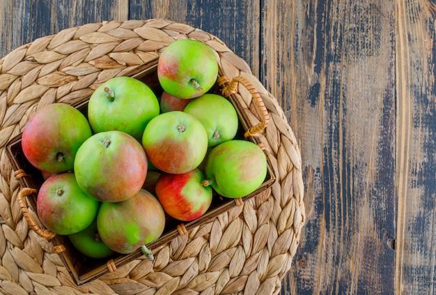 Äpfel in einem korb auf hölzernem und weiden-tischset-hintergrund. flach liegen.