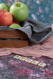 Äpfel in einem rustikalen holztablett auf einem küchentuch