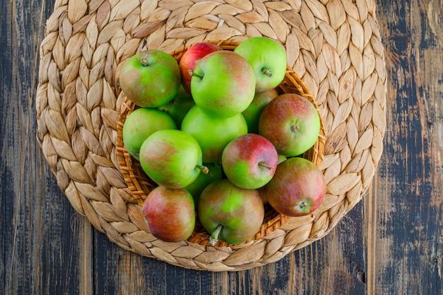 Äpfel in einem weidenkorb auf holz- und tischset-hintergrund. flach liegen.