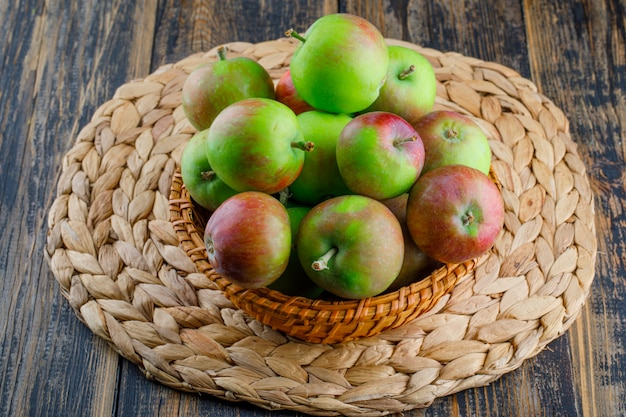 Äpfel in einem weidenkorb auf holz- und tischset-hintergrund. high angle view.