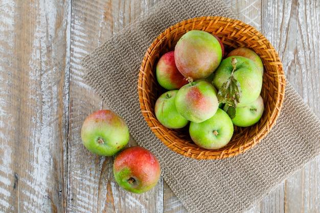 Äpfel in einem weidenkorb auf holz und tischset ..
