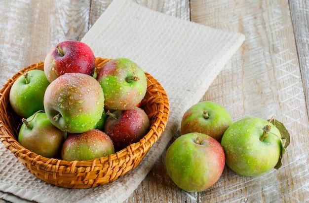 Äpfel in einem weidenkorb mit hohem blickwinkel auf holz- und küchentuch