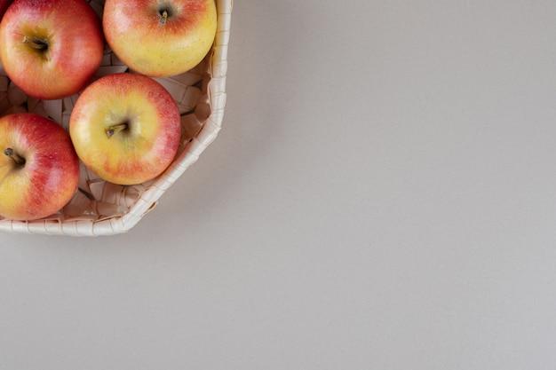 Äpfel in einem weißen korb auf marmor
