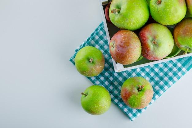 Äpfel in einer holzkiste auf weißem und picknicktuch ..