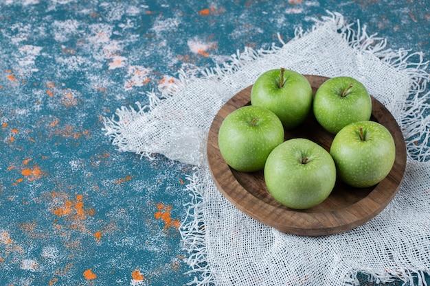 Äpfel in einer holzplatte auf einem blauen texturtisch.