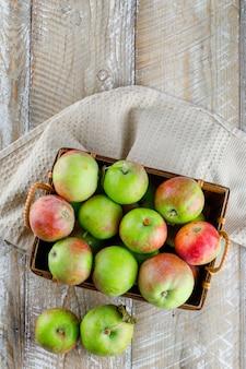 Äpfel in einer korb-draufsicht auf holz- und küchentuch