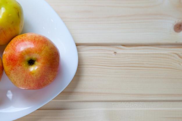 Äpfel in einer schüssel auf einem holztisch