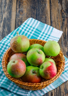 Äpfel in einer weidenkorb-hochwinkelansicht auf holz- und picknicktuchhintergrund
