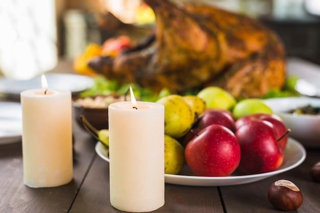 Äpfel mit birnen auf platte mit kerzen