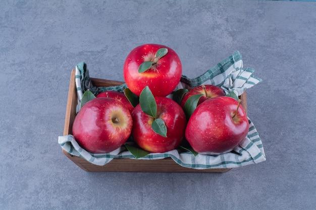 Äpfel mit blättern auf handtuch auf einer schachtel auf der dunklen oberfläche