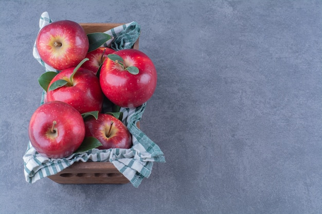 Äpfel mit blättern auf handtuch auf einer schachtel auf marmortisch.