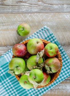Äpfel mit blättern in einem weidenkorb auf holz- und picknicktuch