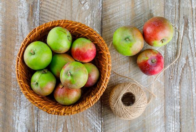 Äpfel mit fadenball in einem weidenkorb auf holz