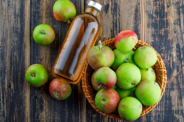 Äpfel mit flasche getränk in einem korb auf hölzernem hintergrund, flach liegen.