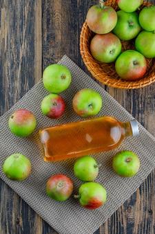 Äpfel mit getränk in einem korb auf holz- und tischset-hintergrund, draufsicht.