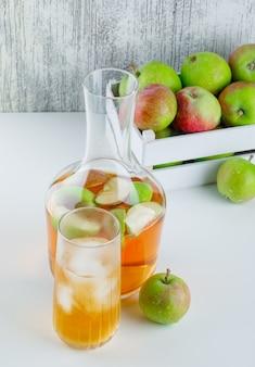 Äpfel mit getränken in einer holzkiste auf weißem und schmuddeligem blickwinkel.