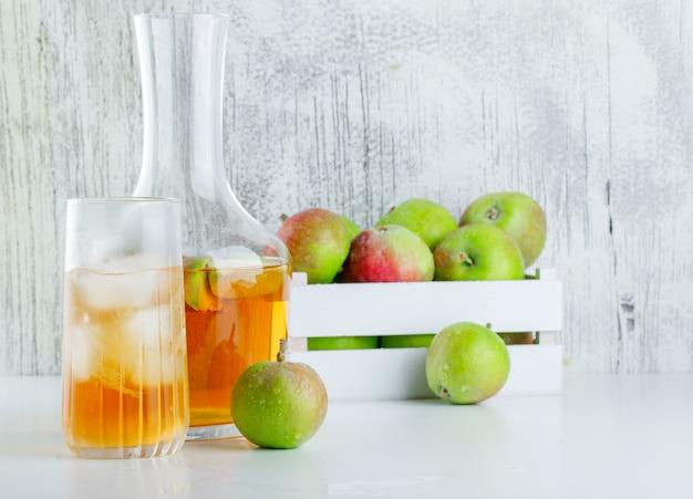 Äpfel mit getränken in einer holzkiste auf weißer und schmuddeliger seitenansicht.